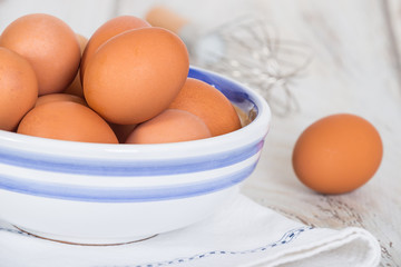 Cage free, brown eggs in a white and blue bowl on kitchen table, close-up. A whisk in the background.