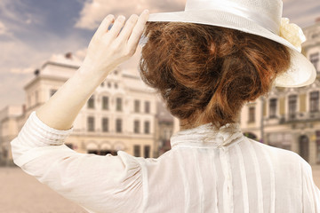 Retro styled picture of woman in victorian hat looking at the city street in Europe