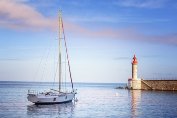Beautiful white yacht on the sea, in the background of a lighthouse and sunset in gentle pink tones