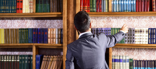 Man takes book from bookcase.