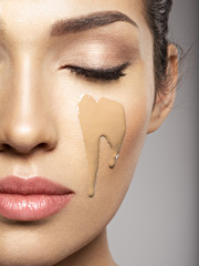 liquid cosmetic makeup foundation is on the female face