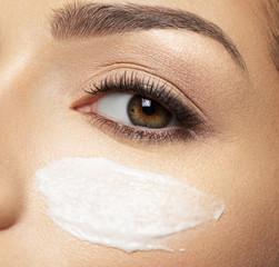 cosmetic cream smear on face near eye