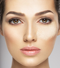 dry cosmetic makeup powder is on the female face.