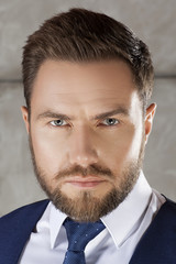 Man wearing blue suit and tie. Modern hair style, beard. Grey background