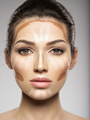 Cosmetic makeup tonal foundation is on woman's face.