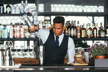 Expert bartender adding alcohol to a shaker
