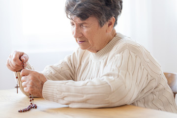 Thoughtful elderly woman praying to god while holding red rosary with cross