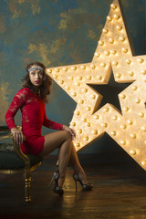 A sexy young girl with red lips and with a rim in her hair in a luxurious reddress and high heels sits in chair in a rich studio interior with gold and a light star