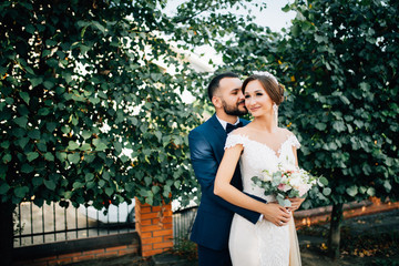 Wedding couple. happy bride and groom embrace and laugh at the background of green leaves.