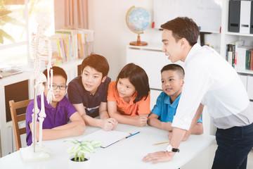 Asian teacher explains a human body structure to little pupil.