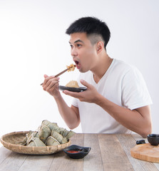 A man is going to eat delicious zongzi(rice dumpling) on Dragon Boat Festival, Asian   traditional food, white background