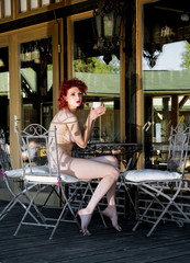 Beautiful redhead nude woman sitting on the terrace near the house