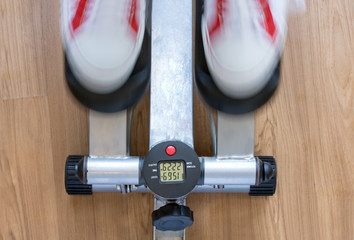 Exercise on a stepping machine, looking from above. Active person with sport shoes exercising on stepper on wooden floor, close up.