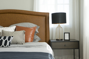 Black and brown pattern pillows setting on bed with brown leather headboard