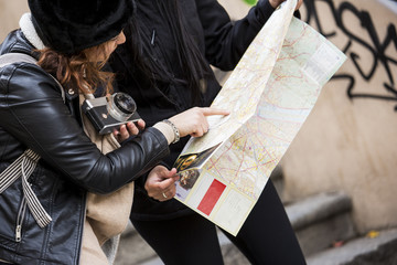 due viaggiatrici si consultano con una mappa per ritrovare la strada in mezzo a una scalinata