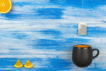 The Cup of tea on a blue background. Tea bag and orange slices. Summer