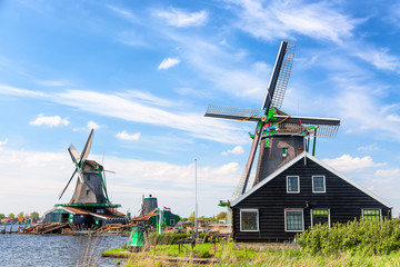 Dutch typical landscape. Traditional old dutch windmills against blue cloudy sky in the Zaanse Schans village, Netherlands. Famous tourism place.