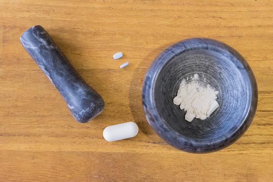 Mortaio con pestello e pillole su tavolo di legno chiaro