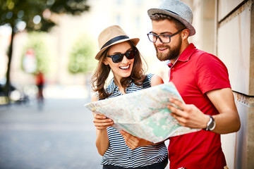 Young couple looking at map while on vacation during summer together Wall mural