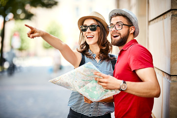 Young couple looking at map and pointing on vacation together in the summer