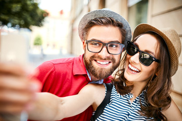 Portrait of cheerful young couple taking selfie together in the summer outdoors