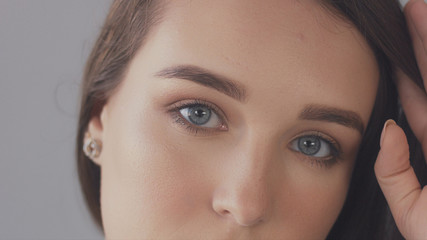 closeup of blue eyes of young woman looking at camera, Studio light ideal strobbing skin highlight