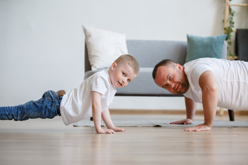 Image of young father and son pushing up on floor against sofa