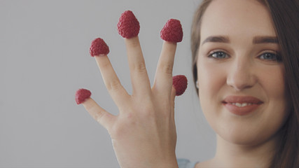 young caucasian woman with straight long hair eats raspberry from fingers. Hand with fingers with raspberry. Model have fun.