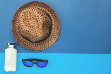 Table top view aerial image of summer & travel beach holiday in the season background concept.Flat lay sun block protection lotion & sun glasses with hat on modern blue paper and copy space design.