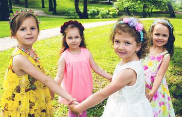 Little elegant girls play in a summer garden, a children's round dance
