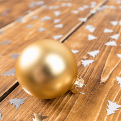 gold christmas ball on a wooden background