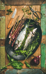 Cooking fish dinner. Flat-lay of raw incooked sea bass with herbs and vegetables over rustic wooden background, top view. Helathy, clean eating, dieting food concept