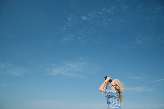 Beautiful natural blonde woman looking through binoculars against blue sky
