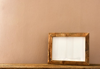 Empty wooden picture frame with rustic style design placed on wooden shelf. Classic color theme in minimalist style.