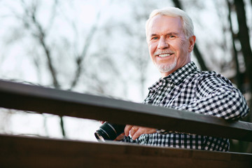 First photo. Low angle of positive mature man utilizing camera and smiling to camera