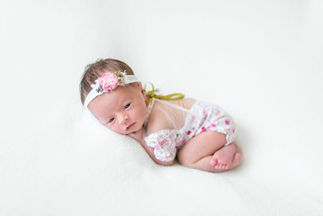 Lovely newborn girl in flowery dress laying on her belly