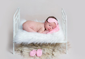 Dreamy baby girl lying curled on stomach on small crib.