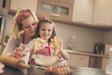 Little girl baking dough with her mother