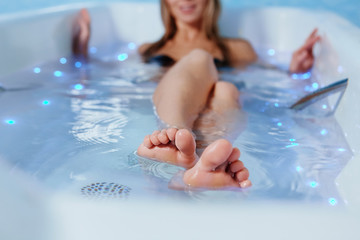 Legs of a beautiful girl on the background of water in the Jacuzzi