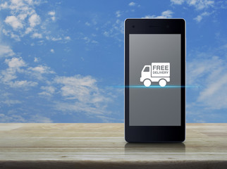 Free delivery truck icon on modern smart phone screen on wooden table over blue sky with white clouds, Business transportation concept