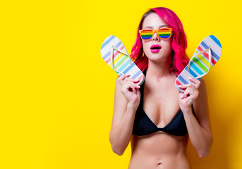 Young pink hair girl in bikini and rainbow glasses with flip flops. Portrait isolated on yellow background