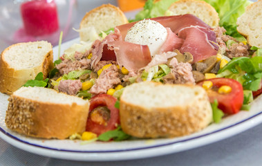 Close-up of a fresh salad on a plate. Healthy food. Slices of bread,  lettuce, tomato, mozzarella, corn, mushrooms and slice of  ham