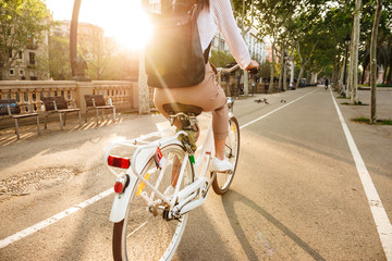 Back view image of young lady on bicycle on the street. Fototapete