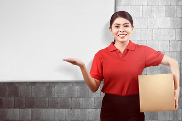 Young asian delivery woman carrying parcel and showing copyspace
