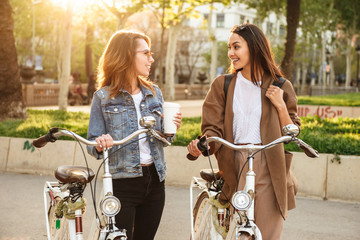 Two young happy women friends outdoors with bicycles