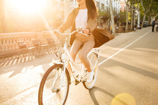 Cropped photo of young lady on bicycle on the street.