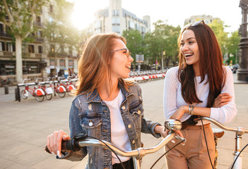 Two young beautiful women friends outdoors with bicycles
