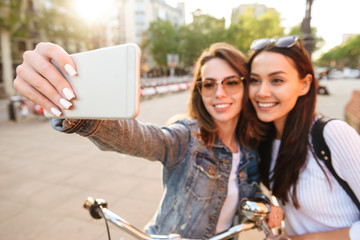Young beautiful women friends make selfie by mobile phone.