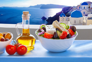 Greek salad against famous church in Oia village, Santorini island in Greece