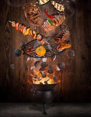 Kettle grill with hot briquettes, cast iron grate and tasty beef steaks flying in the air.